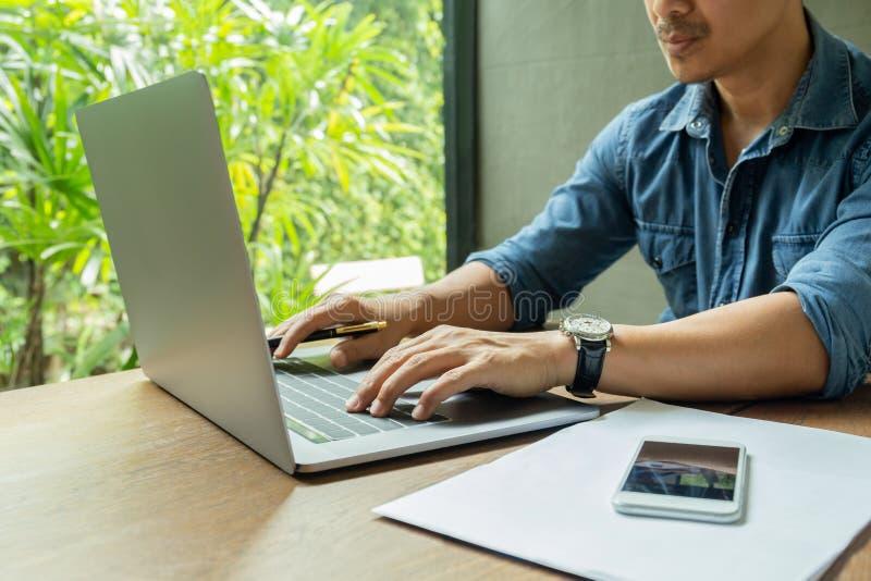 Geschäftsmann, der an Laptop mit Smartphone und Schreibarbeit auf Tabelle arbeitet stockfotografie