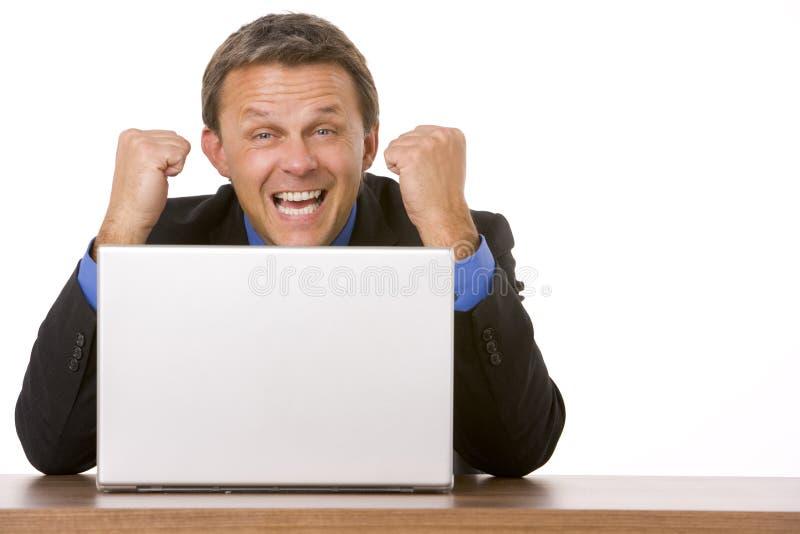 Geschäftsmann, der am Laptop zujubelt stockbilder