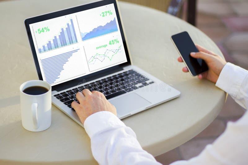 Geschäftsmann, der Laptopschirm mit Geschäftsdiagrammen betrachtet lizenzfreie stockfotos