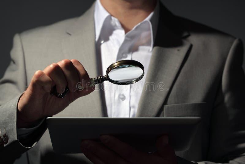 Geschäftsmann, der Lupe und digitale Tablette hält stockfotos