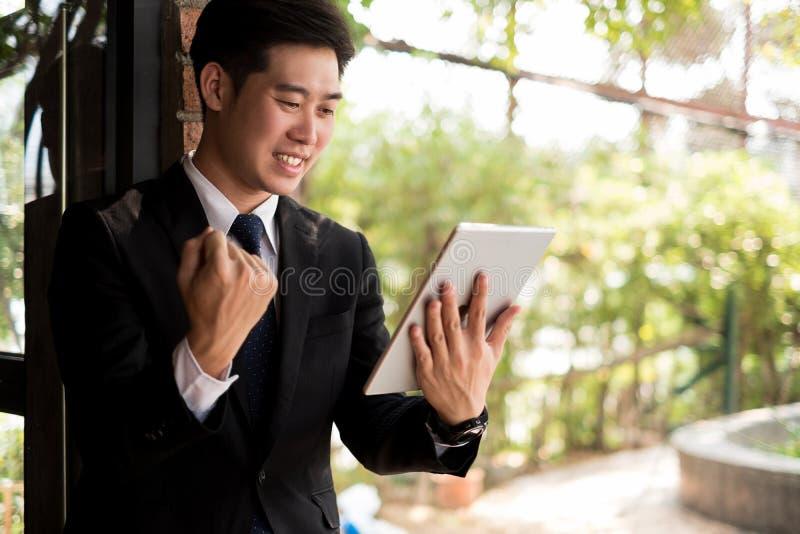 Geschäftsmann, der mit den Armen herauf das Feiern für Erfolgsarbeit im Büro, Geschäftskonzept, Erfolgskonzept lächelt lizenzfreies stockbild