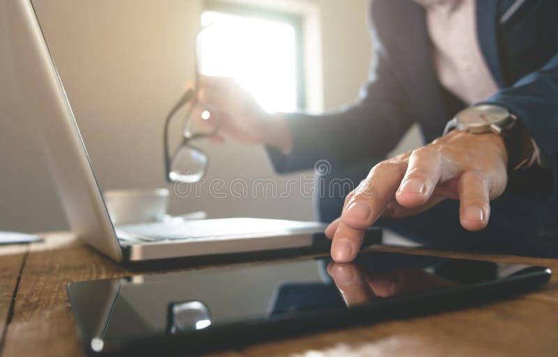 Geschäftsmann, der mit digitaler Tablette und Laptop mit Finanzgeschäftsstrategie an einem Arbeitsplatz arbeitet lizenzfreie stockfotos