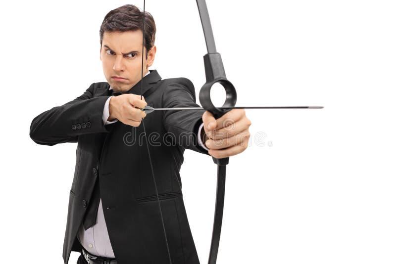 Geschäftsmann, der mit einem Pfeil und Bogen zielt lizenzfreies stockbild