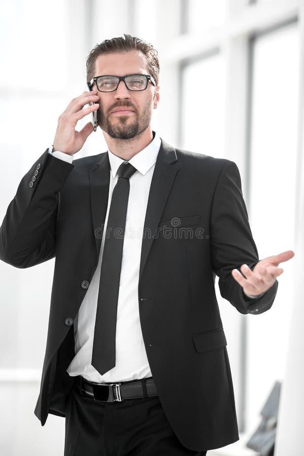 Geschäftsmann, der mit einem Teilhaber in einem Handy spricht stockfotos