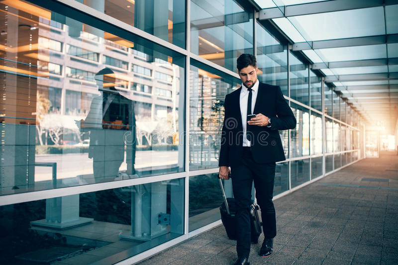 Geschäftsmann, der mit Gepäck geht und Handy am airpo verwendet lizenzfreie stockbilder