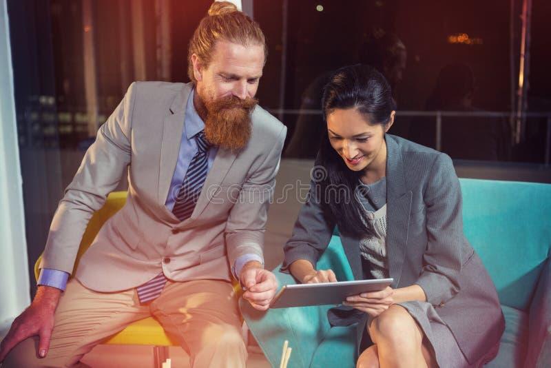 Geschäftsmann, der mit Kollegen auf digitaler Tablette sich bespricht lizenzfreies stockbild