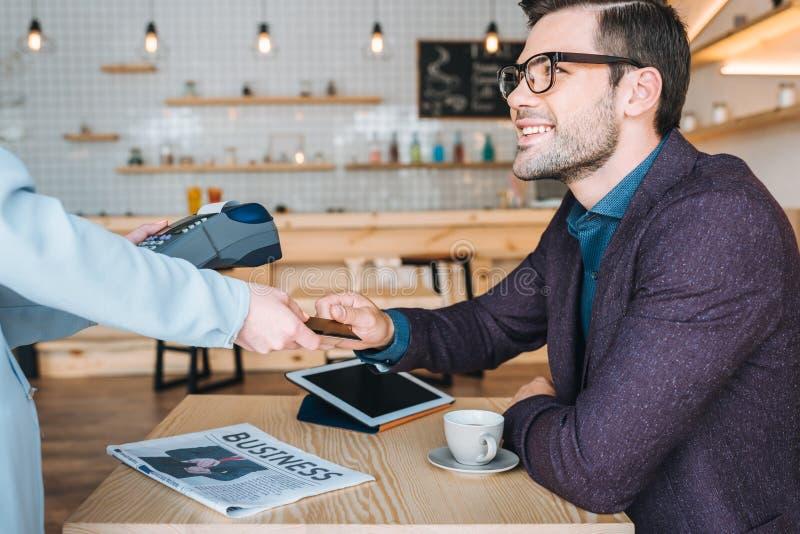 Geschäftsmann, der mit Kreditkarte im Café zahlt lizenzfreies stockfoto