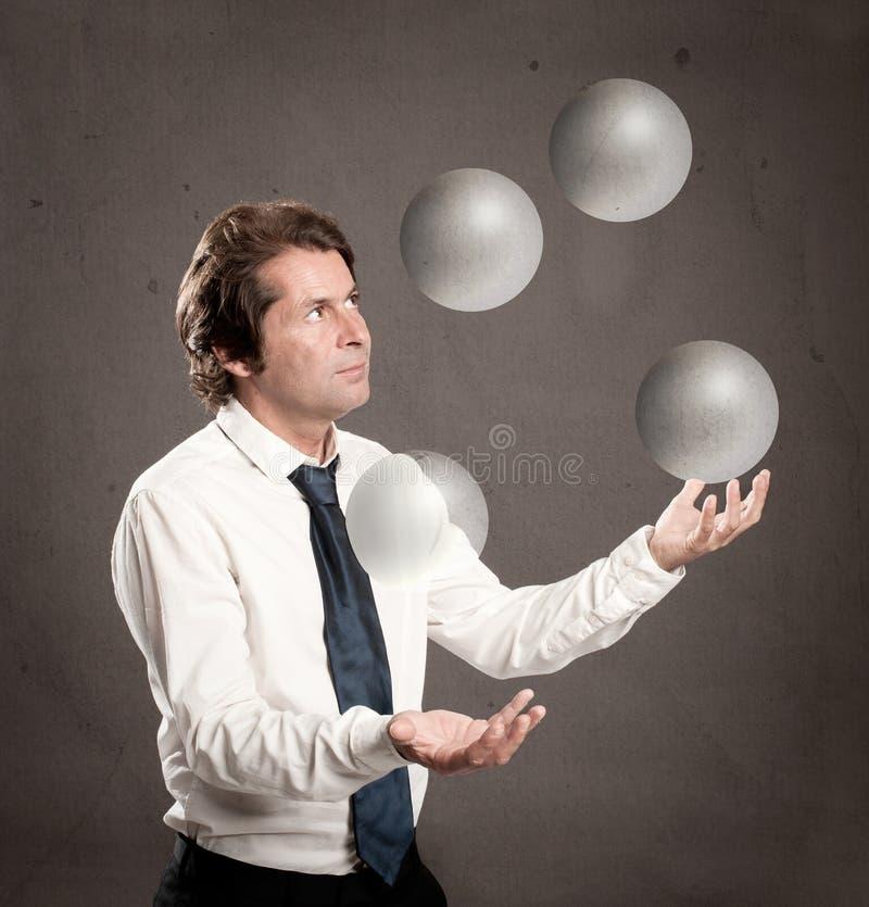 Geschäftsmann, der mit Kristallbereichbällen jongliert stockfotografie