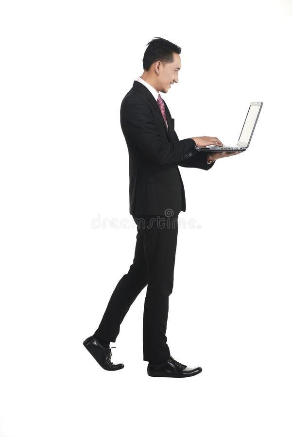 Geschäftsmann, der mit Laptop arbeitend steht lizenzfreie stockfotografie