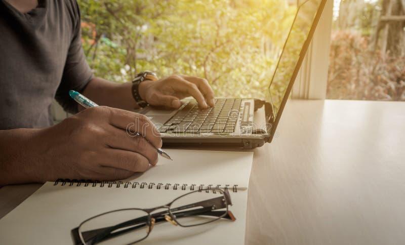 Geschäftsmann, der mit Laptop-Computer Sitzen arbeitet stockbild