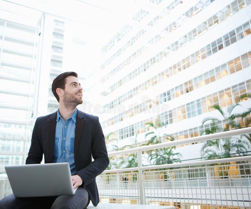 Geschäftsmann, der mit Laptop innerhalb des Gebäudes sitzt stockfoto