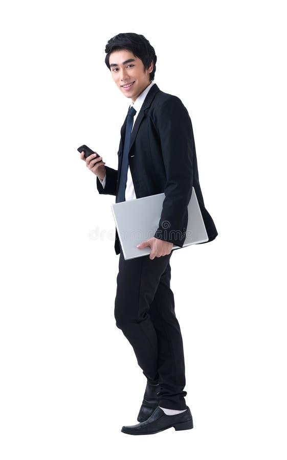 Geschäftsmann, der mit Laptop und Telefon steht stockfotografie