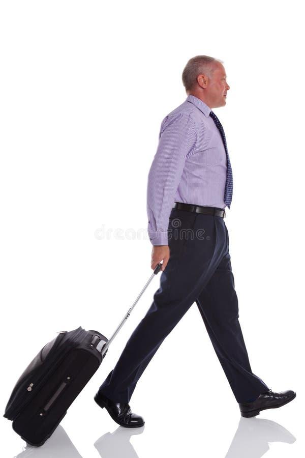 Geschäftsmann, der mit Reisekoffer geht. lizenzfreie stockfotos