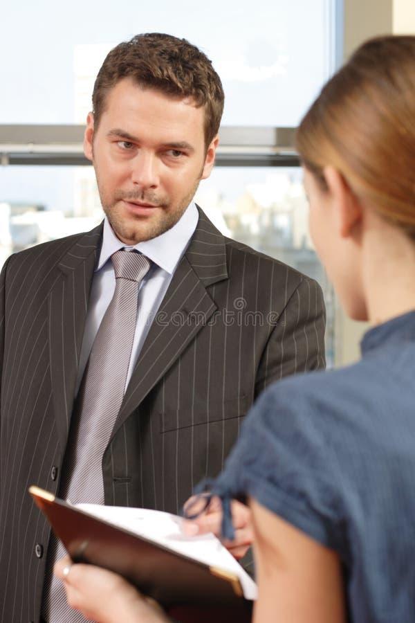 Geschäftsmann, der mit seinem Sekretär im Büro spricht lizenzfreies stockfoto