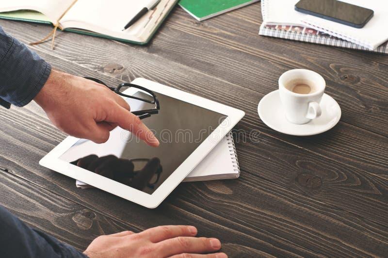 Geschäftsmann, der mit Tablet-Computer am Büro oder am Haus arbeitet stockfoto