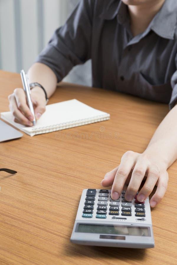 Geschäftsmann, der mit Taschenrechner und Notizblock auf Schreibtisch arbeitet lizenzfreie stockfotos