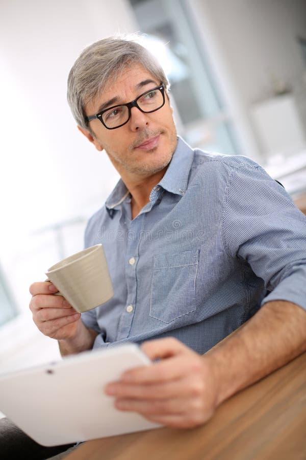 Geschäftsmann, der mit Tasse Kaffee sich entspannt lizenzfreie stockfotos