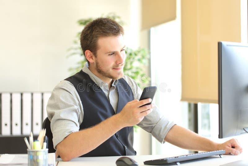 Geschäftsmann, der mit Telefon und Computer arbeitet lizenzfreie stockfotos