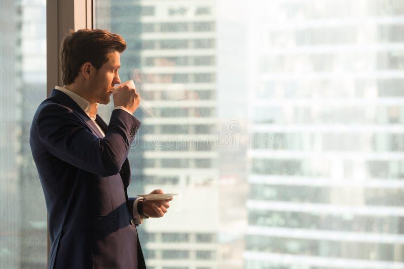 Geschäftsmann, der Morgenkaffee im Büro genießt lizenzfreie stockbilder