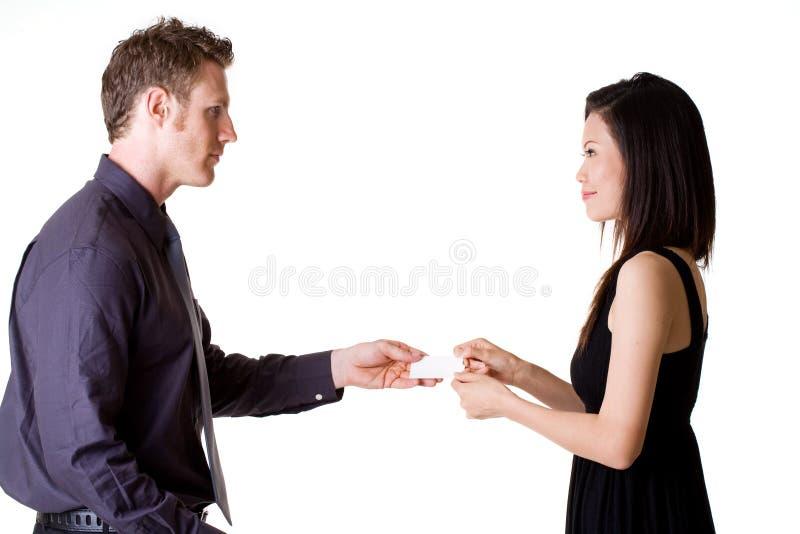 Geschäftsmann, der Namenskarten mit Frau austauscht stockbild