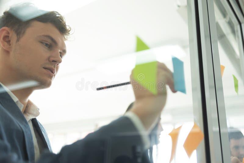 Geschäftsmann, der neue Ideen schreibt stockbild