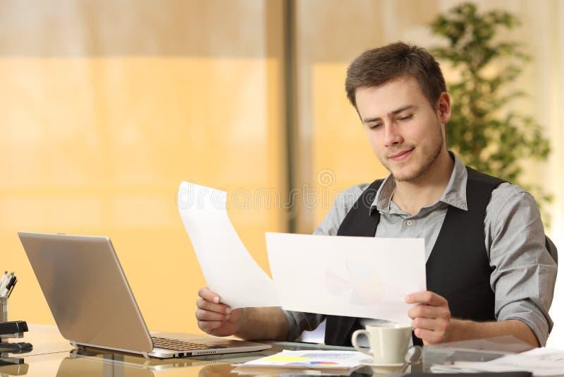 Geschäftsmann, der Papierdokumente vergleichend arbeitet lizenzfreies stockfoto