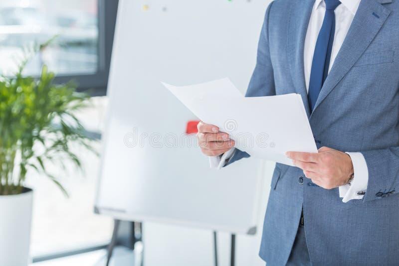Geschäftsmann, der Papiere in den Händen im Büro hält lizenzfreies stockbild