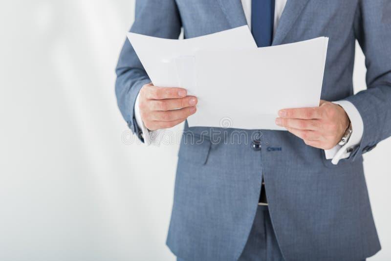 Geschäftsmann, der Papiere in den Händen im Büro hält stockfotos