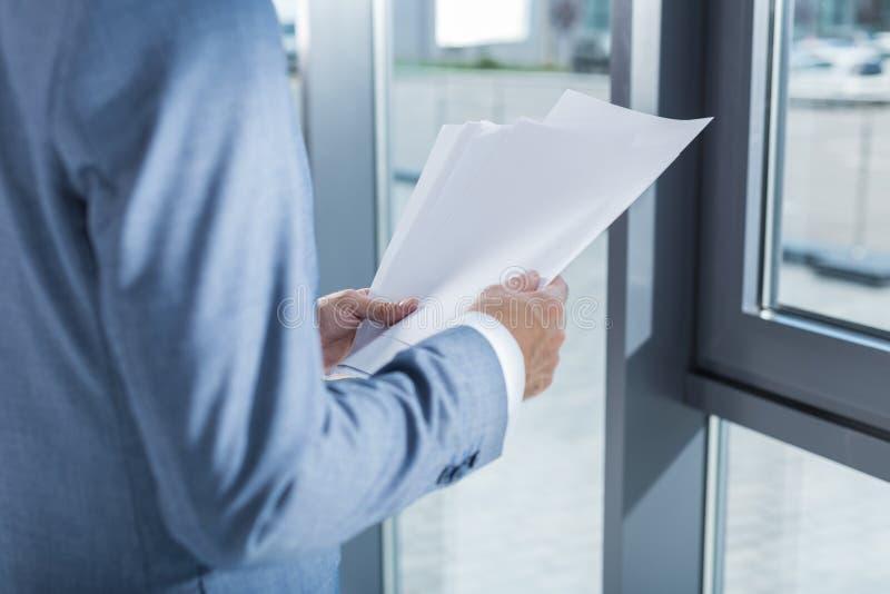 Geschäftsmann, der Papiere in den Händen im Büro hält lizenzfreie stockbilder