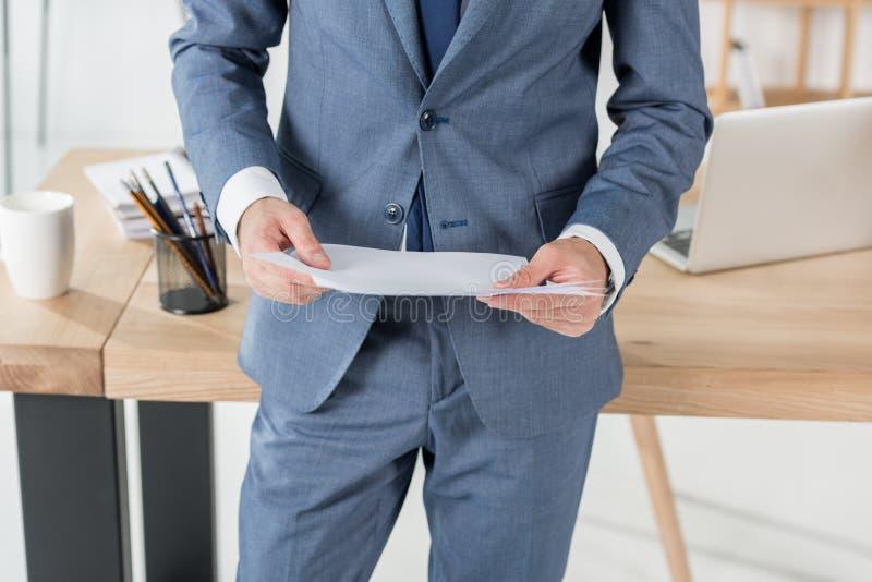 Geschäftsmann, der Papiere in den Händen im Büro hält stockbild
