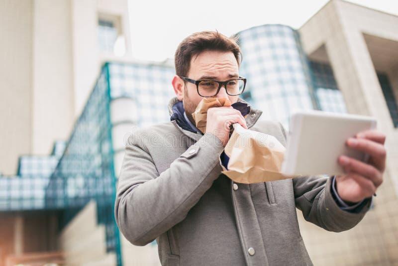 Geschäftsmann, der Papiertüte über Mund hält, als ob, eine Panikattacke habend lizenzfreies stockbild