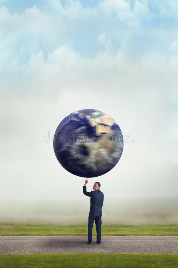 Geschäftsmann, der Planetenerde mit einem Finger hält stockfotografie