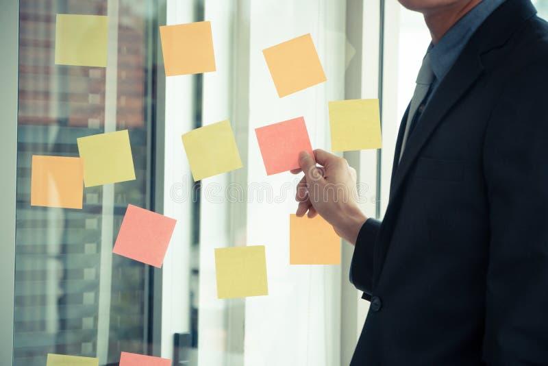 Geschäftsmann, der Projektplan und -aufgabe im beweglichen Prozess für Team im Konferenzzimmer für GeistesblitzGeschäftsstrategie lizenzfreie stockfotos