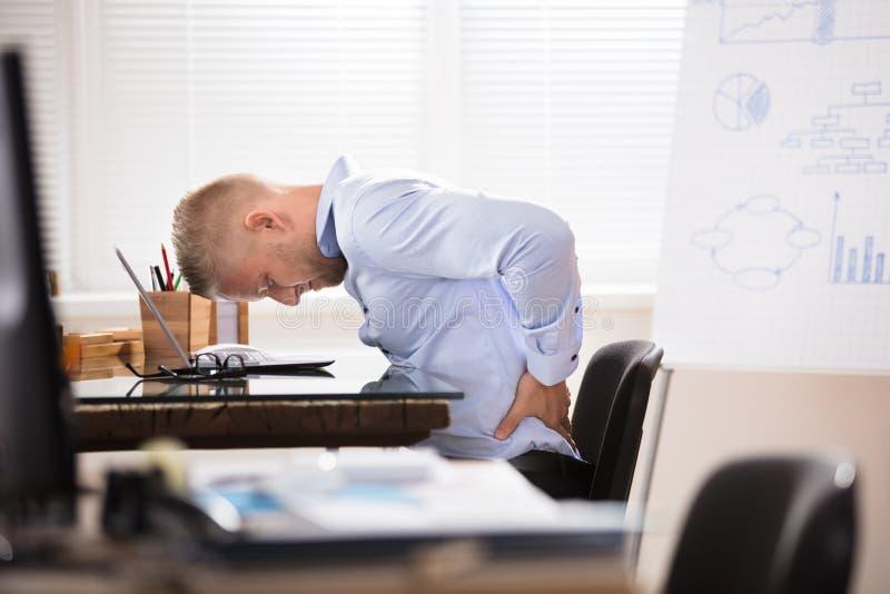 Geschäftsmann, der Rückenschmerzen hat lizenzfreie stockbilder