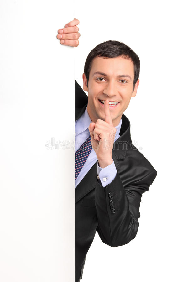 Geschäftsmann, der Ruhe, hinter weißes Panel gestikuliert lizenzfreies stockfoto
