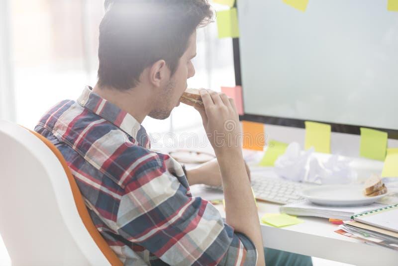 Geschäftsmann, der Sandwich beim Sitzen am Computertisch isst stockfotografie