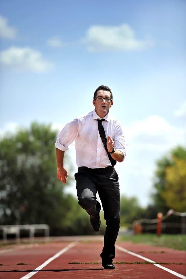Geschäftsmann, der schnell auf athletischer Bahn im Belastungs- und Dringlichkeitskonzept läuft stockfotos