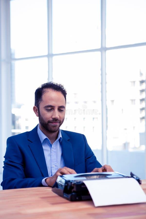 Geschäftsmann, der an Schreibmaschine beim Sitzen am Schreibtisch im Büro arbeitet stockbild