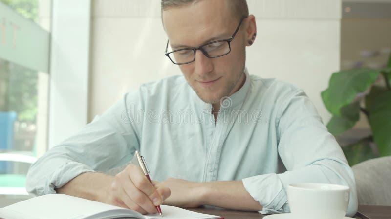 Geschäftsmann, der a schreibt, um Liste in einem Geschäftsplaner zu tun lizenzfreies stockbild