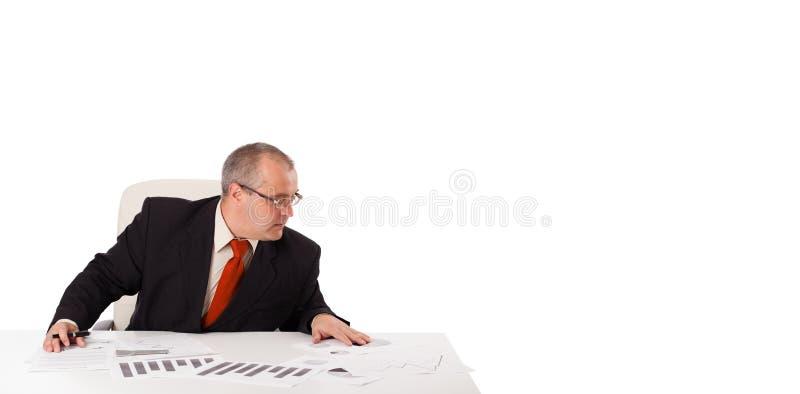 Geschäftsmann, der am Schreibtisch mit Exemplarplatz sitzt lizenzfreie stockbilder