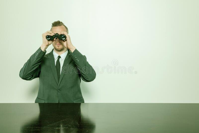 Geschäftsmann, der am Schreibtisch mit Ferngläsern sitzt lizenzfreie stockfotografie