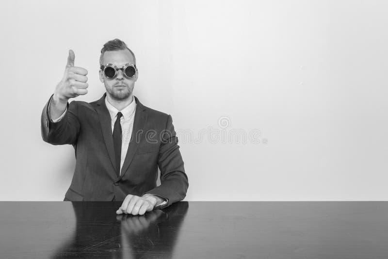 Geschäftsmann, der am Schreibtisch mit Ferngläsern sitzt stockfoto