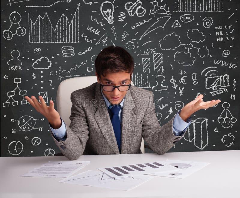 Geschäftsmann, der am Schreibtisch mit Geschäftsentwurf und -ikonen sitzt lizenzfreies stockbild