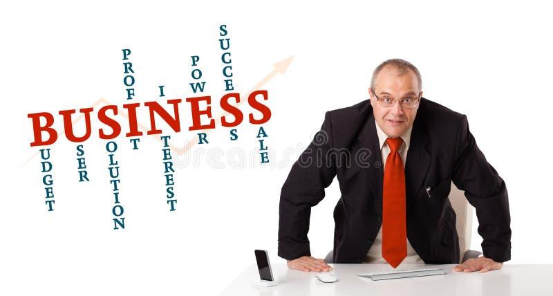 Geschäftsmann, der am Schreibtisch mit Geschäftswortwolke sitzt stockfotografie
