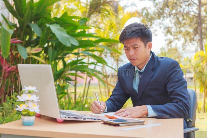 Geschäftsmann, der am Schreibtisch mit Internet-Radioapparat arbeitet lizenzfreie stockfotografie