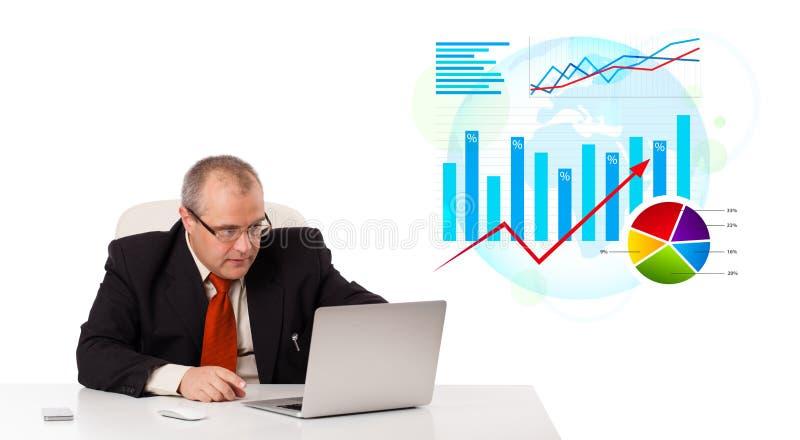 Geschäftsmann, der am Schreibtisch mit Laptop und Statistiken sitzt lizenzfreies stockbild