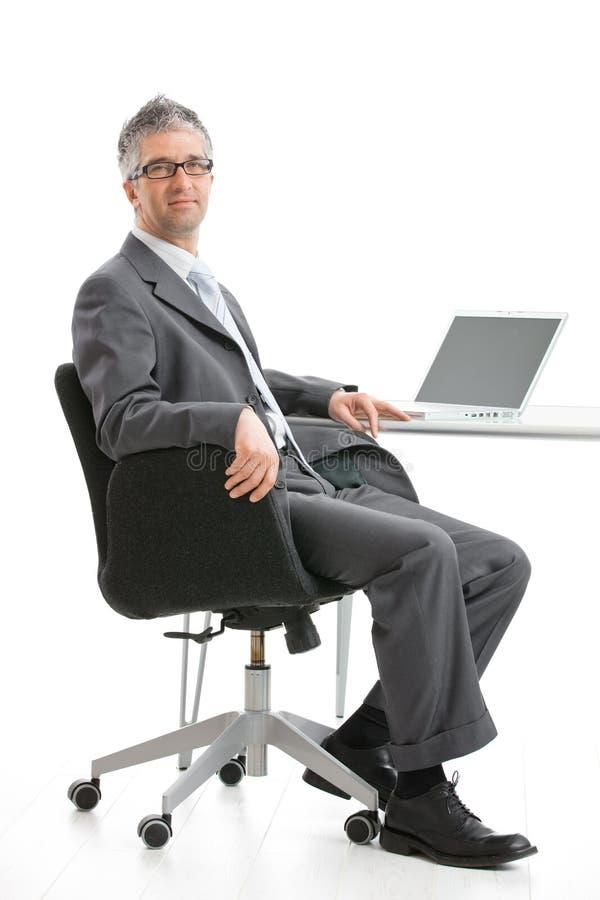 Geschäftsmann, der am Schreibtisch sitzt lizenzfreies stockbild