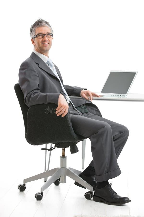 Geschäftsmann, der am Schreibtisch sitzt stockfotografie