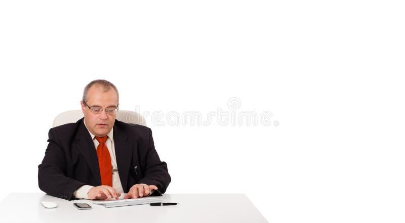 Geschäftsmann, der am Schreibtisch sitzt und auf Tastatur mit Kopie sca schreibt stockbilder