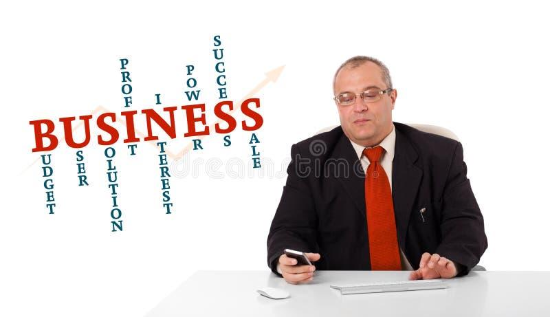 Geschäftsmann, der am Schreibtisch sitzt und ein Mobiltelefon mit busin hält lizenzfreie stockfotografie
